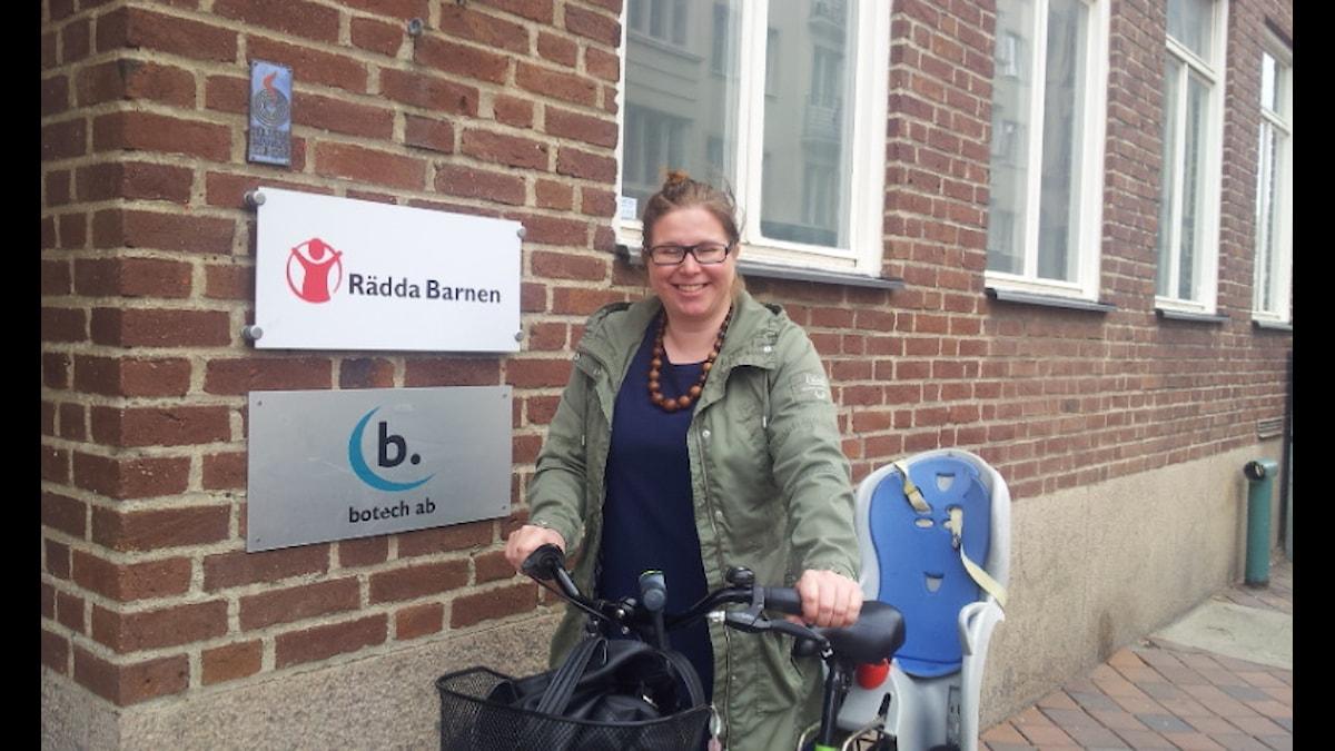 Taru Viinikainen taluttaa lastenisutuimella varustettua polkupyörää ja hymyilee kameralle.
