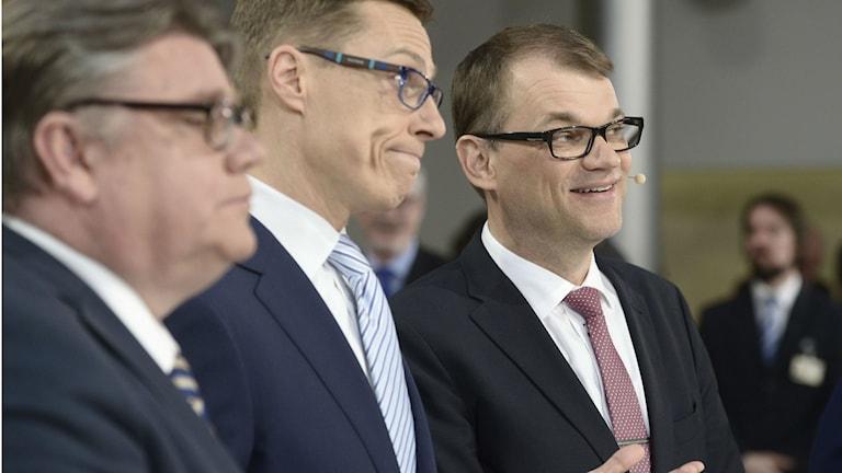 Timo Soini, Alexander Stubb ja Juha Sipilä poseeraavat puvut päällä ja silmälaseissa ja muistuttavat paljon toisiaan.