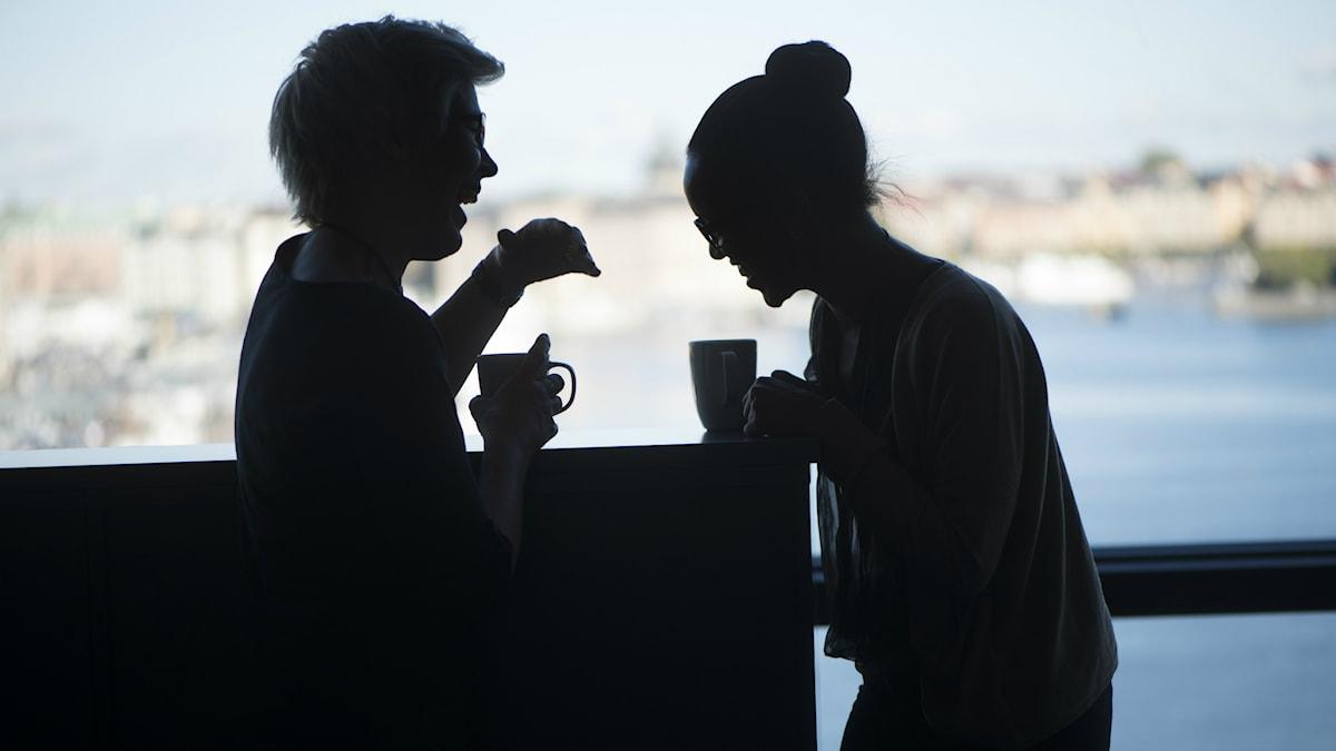 Kaksi naista nauraa kahvitauolla työpaikallaan.