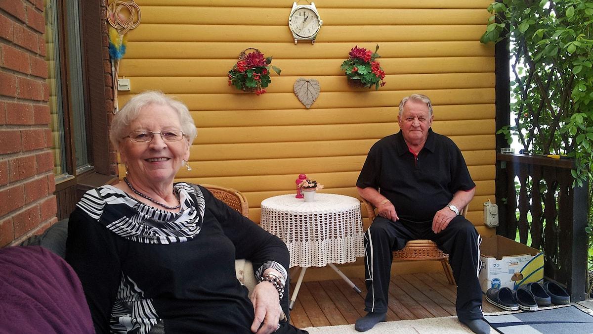 Eila ja Onni Riihimäki verannallaan. Eila istuu hymyilevänä sohvalla etualalla, Onni naama peruslukemilla kellertävällä peräseinällä. Kuva/Foto: Anna Tainio, SR Sisuradio