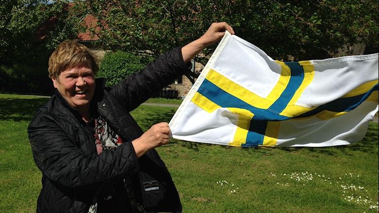 Sisuradion toimittaja Eija Björstrand pitelee ruotsinsuomalaisten lippua kesäisellä radiotalon pihalla. Kuva: Marika Pietilä / Sveriges Radio Sisuradio