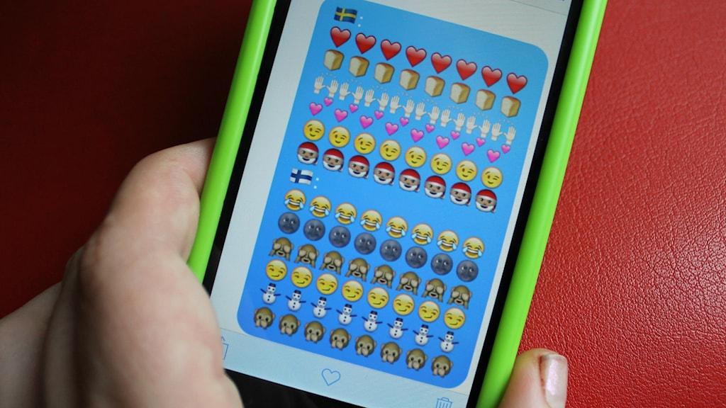 Kuvassa Ruotsin ja Suomen käyttämiä emojeja puhelimen näytöllä.