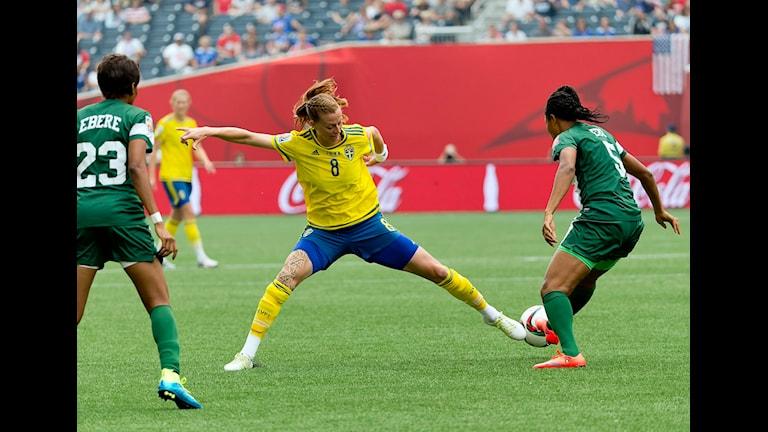 Ruotsin maajoukkueen pelaaja Lotta Schelin taistelee pallosta kahden Nigerian pelaajan kanssa Ruotsin MM-kisojen avausottelussa. Foto: Adam Ihse/TT.