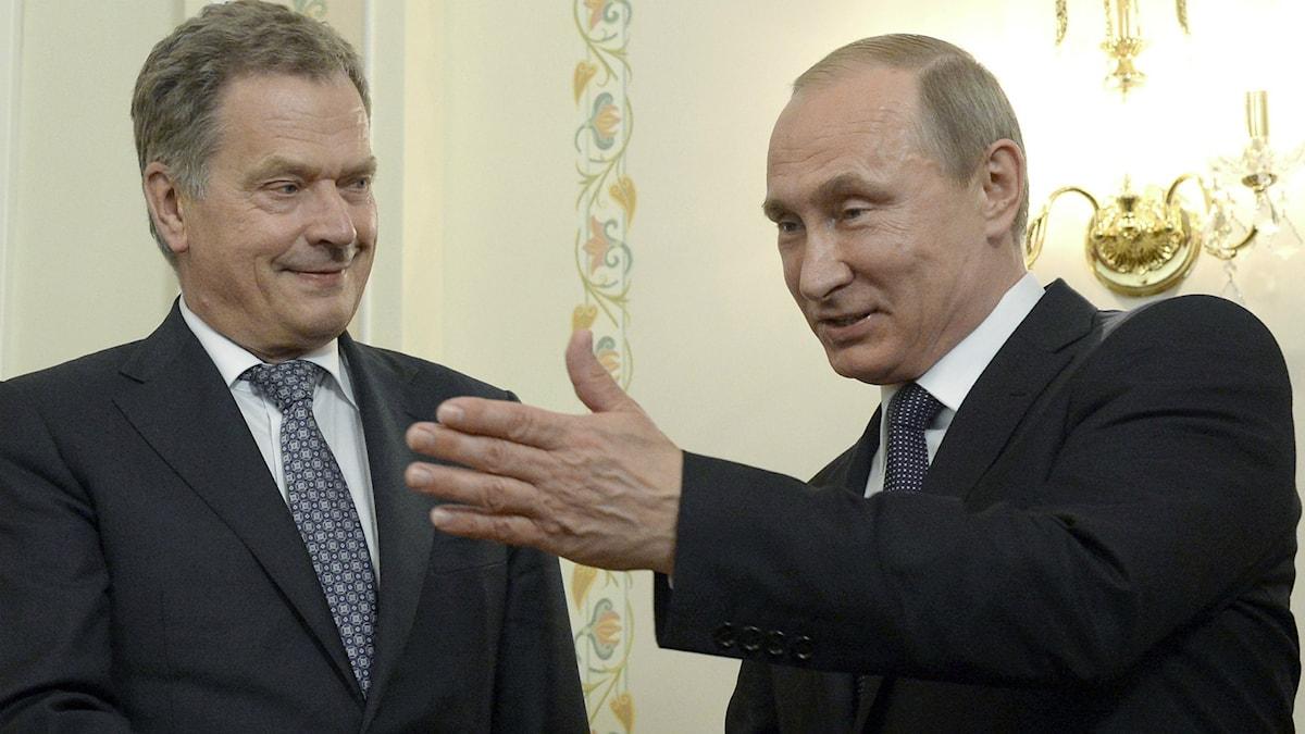 Suomen presidentti Sauli Niinistö vasemmalla katselee Venäjän presidentti Vladimir Putinia joka osoittaa kädellään kuva ulkopuolelle.