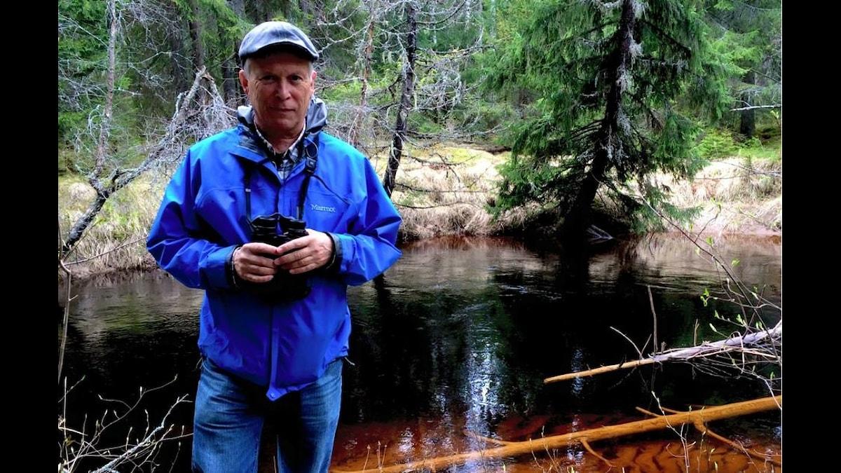 Timo Melakari seisoo metsässä puron varrella.