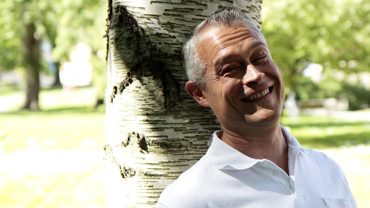 Kesäpuhuja Gabriel Suovanen nojaa koivua vasten ja hymyilee. Foto: Kai Rauhansalo