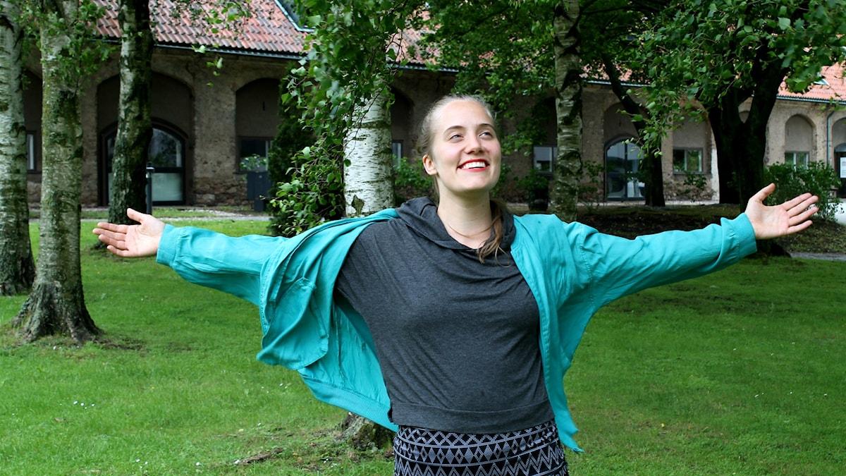 Malou Zilliacus seisoo kädet levällään koivujen edessä. Foto: Kai Rauhansalo