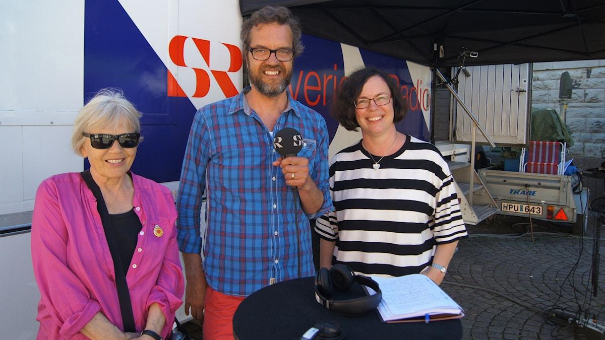 Pirkolla on vaaleanpunainen paita ja aurinkolasit, Pekalla mikrofoni kädessä ja Petralla mustavalko-raidallinen paita ja silmälasit