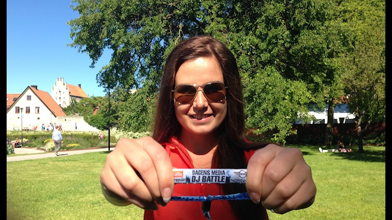 Marika punaisessa paidassaan pitää käsissään Dj Battlen ranneketaa. Taustalla Almedalenin puisto. Kuva: Marika Pietilä / Sveriges Radio Sisuradio