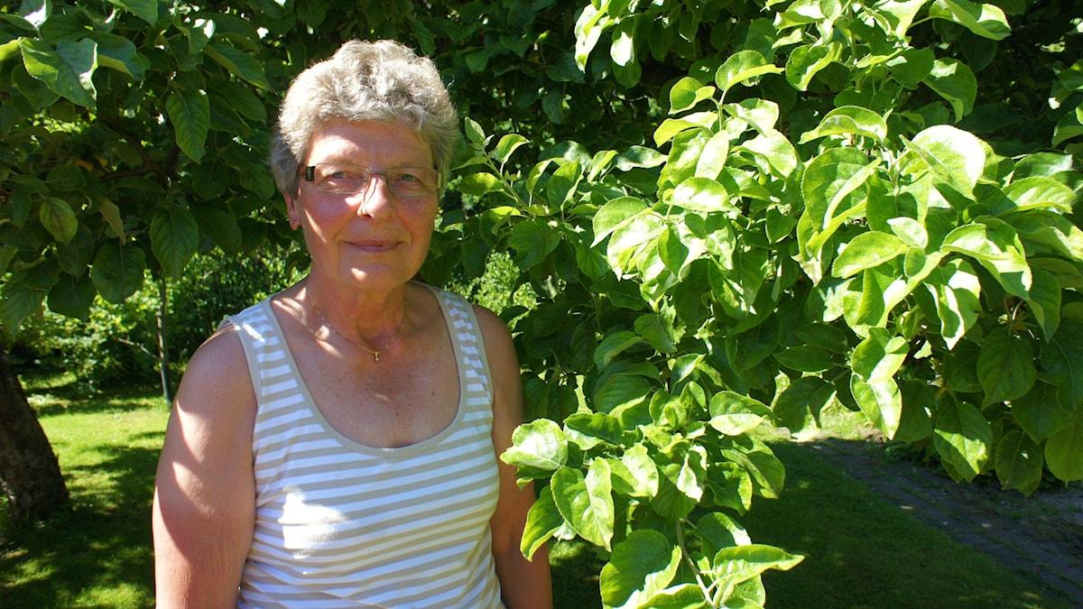 Hilkka Risbergin puutarhassaan lämpimänä kesäpäivänä.