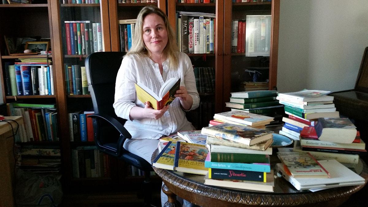 Tuttökirjoja tutkiva Sara Kokkonen  istuu työpöytänsä ääressä. Pöytä on täynnä tyttökirjoja