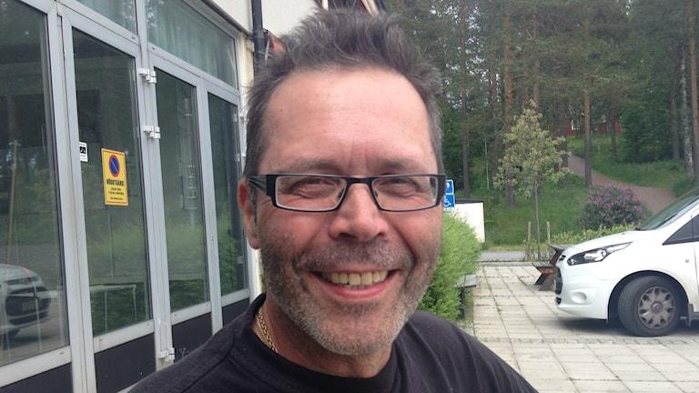 Sänkipartainen, tummatukkainen, silmälasipäinen Keijo Perkiö hymyilee kuvassa, joka on otettu ulkotilassa. Foto: Erpo Heinolainen SR Sisuradio.