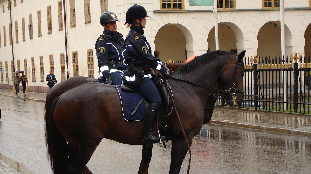 Kaksi poliisia tummien hevosten selässä