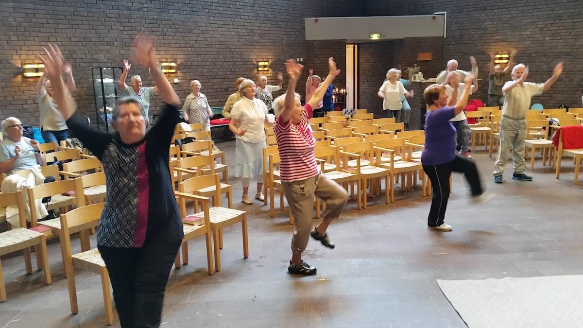 Kuvassa kirkkosalissa vauhdikkaasti jumppaavia ihmisiä.