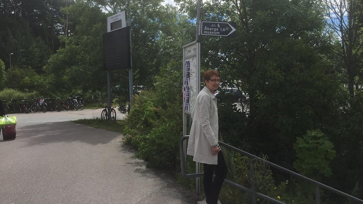 Tarja Nätti seisoo Åbergs Museum -tiekyltin edessä vaalea takki päällä, kuva: Timo Laine/SR Sisuradio