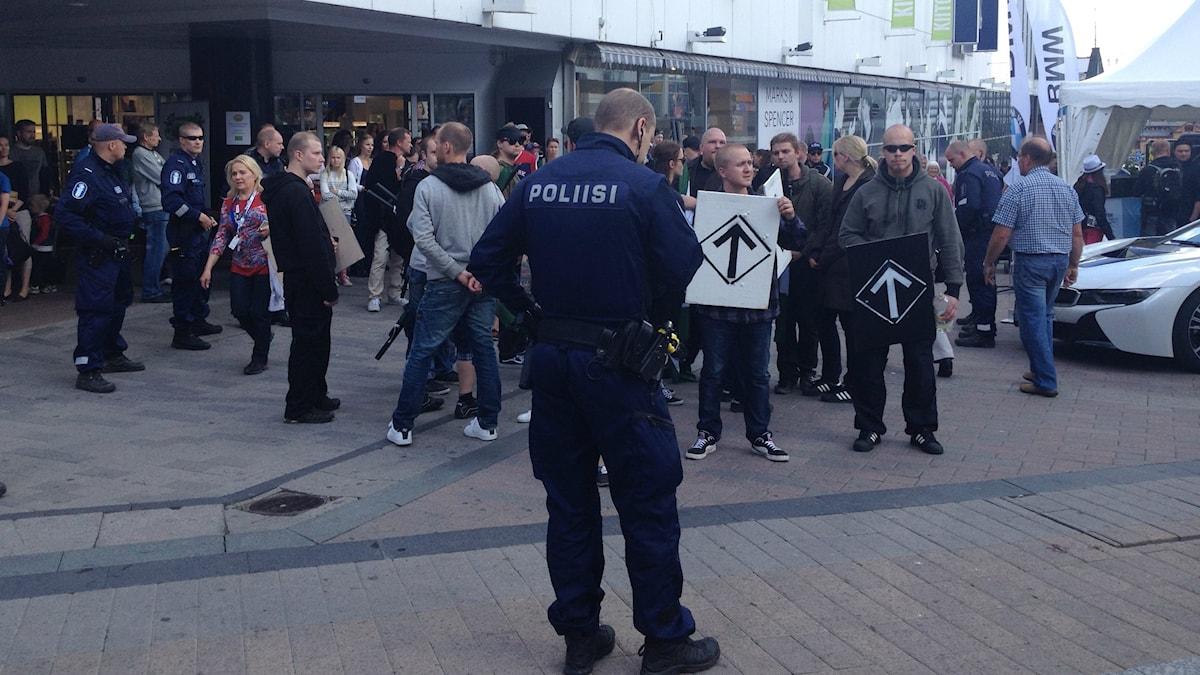 Poliisi seisoo edessä, takana uusnatseja kylttien kanssa, kadulla kävelee ihmisiä