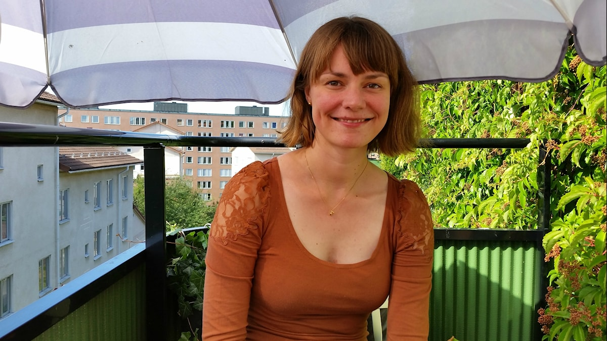 Arkkitehti Pivi Vanamo istuu parvekkeella, auringonvarjon alla.