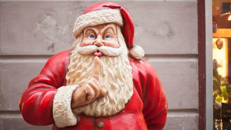 """En jultomte (julskyltning) håller ena pekfingret framför läpparna och """"hyschar""""."""