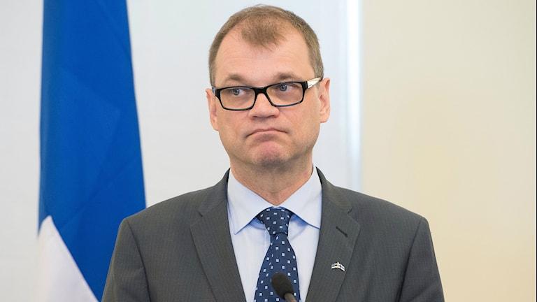 Kuvassa näkyy suomen pääministeri Juha Sipilä, ja hänen taustallaan on Suomen lippu. Foto: Raigo Pajula/TT
