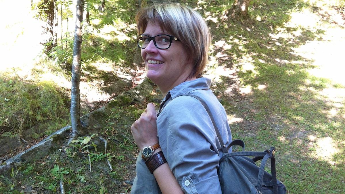 Etnologian professori Outi Fingerroos reppu selässään luonnossa. Foto: Marja Siekkinen