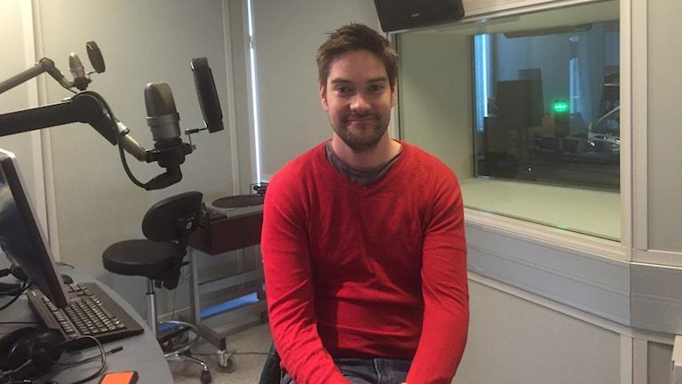 Henri Alén istuu studiossa puinen paita päällään, foto: Timo Laine SR Sisuradio