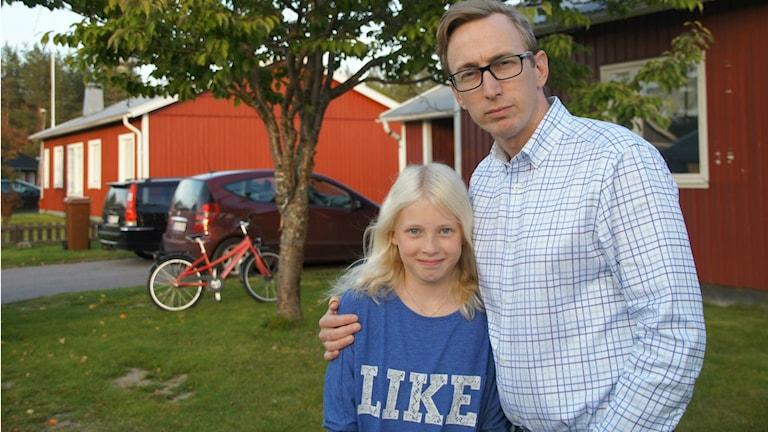 Jennifer ja Robert Pettersson seisovat pihallaan, ja taustalla on kaksi punaista omakotitaloa, punainen polkupyörä ja kaksi autoa. Foto: Pekka Kenttälä/Sveriges Radio Sisuradio
