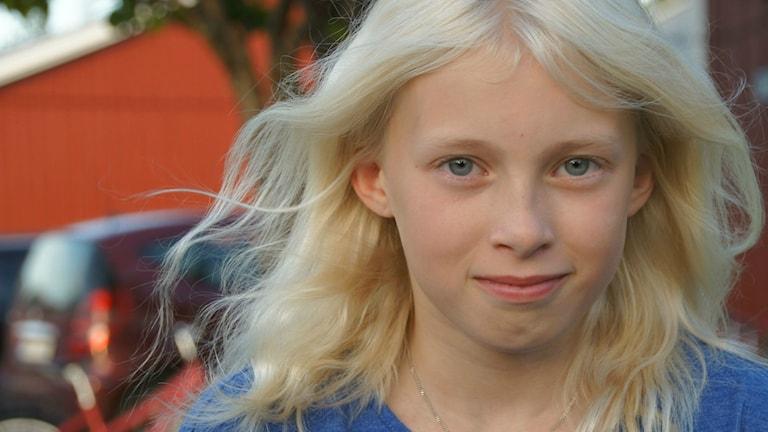 Lähikuva Jennifer Petterssonin kasvoista. Jennifer hymyilee ja hänen vaaleat hiukset heiluvat tuulessa. Foto: Pekka Kenttälä/Sveriges Radio Sisuradio