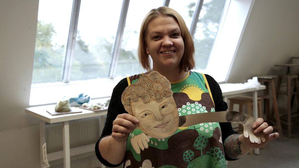Mirre Ketola näyttää piirtämänsä pojan kasvoja. Foto: Kai Rauhansalo
