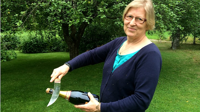 Sommelieeri Leena Jansson näyttää, kuinka samppanja aukeaa sapelilla.