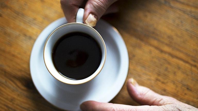 Kuvassa näkyy vanhemman ihmisen kädet, jotka pitelevät kahvikupista.