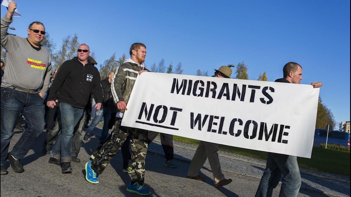 """Kuvassa näkyy marssiva miesjoukko. Kaksi kantaa kylttiä, jossa lukee """"Migrants not welcome""""."""