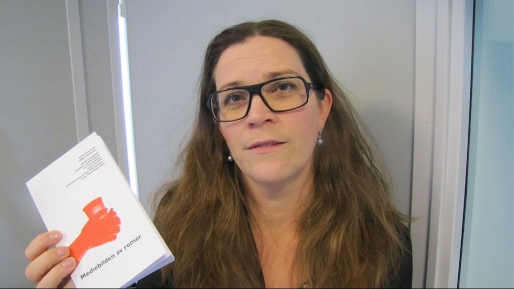 Anna håller sin nya bok i handen, hon har glasögon och brunt hår. Kuva: Elina Härmä / Sveriges Radio Sisuradio