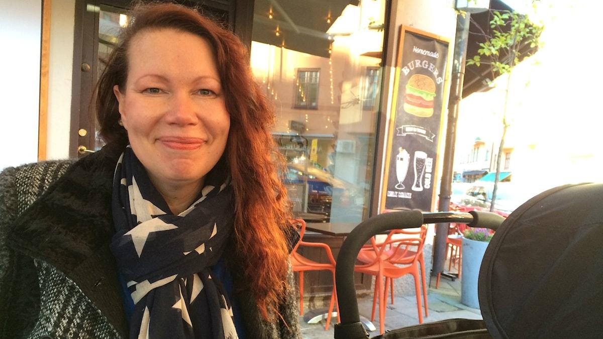 Kuvassa näkyy kahvilan terrassilla istuva, ruskeatukkainen hymyilevä nainen jolla on lastenvaunut vieressään.