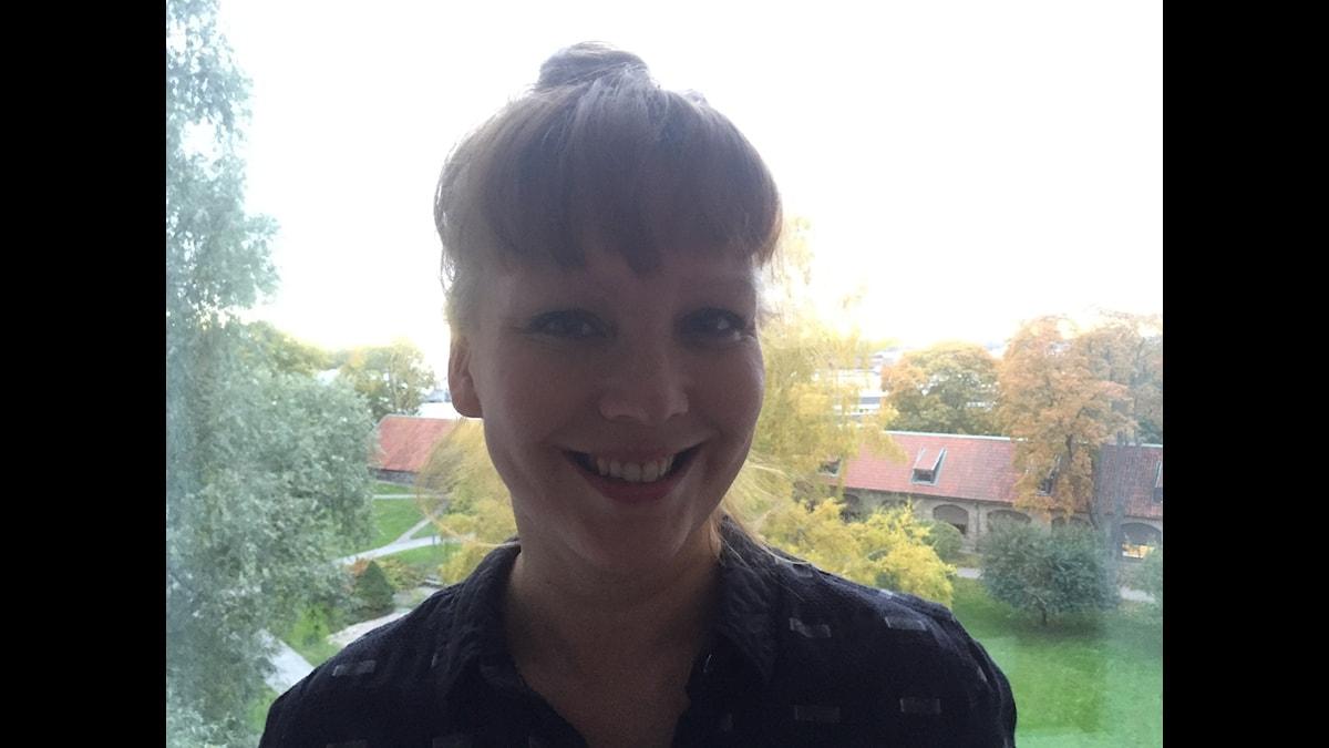 Tiia Vanhatapio seisoo ikkunan ääressä ja takaa näkyy vihreä sisäpiha. Foto: Tuomas MacGilleon/SR Sisuradio.