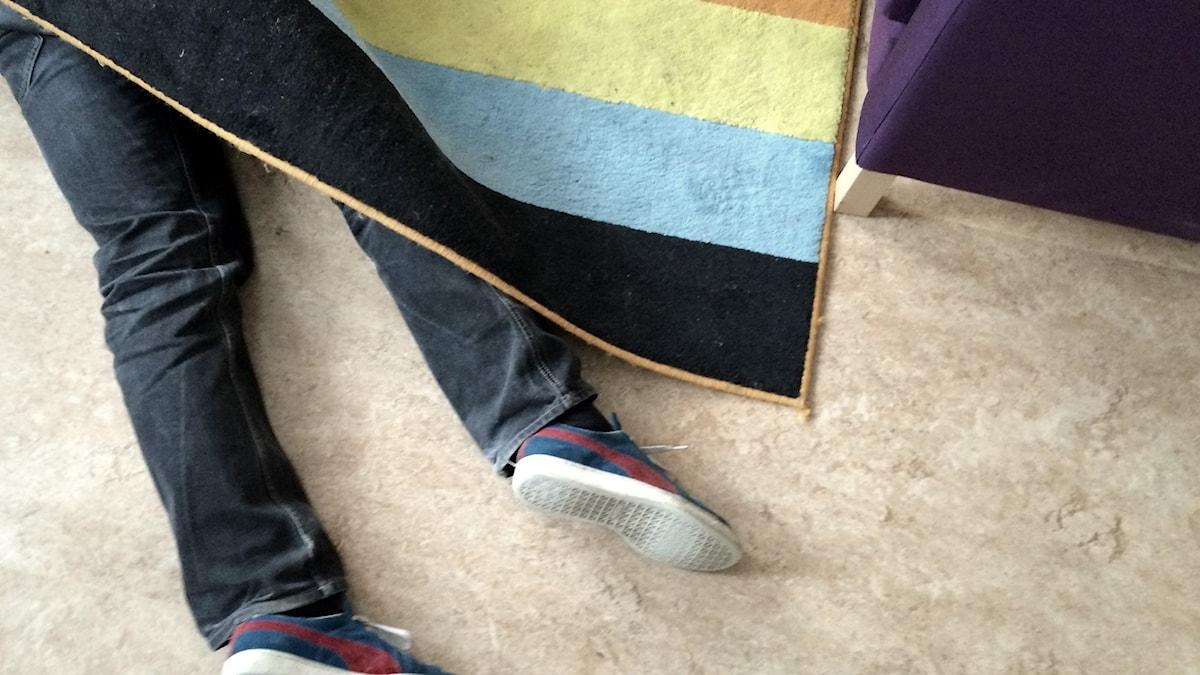Jalat näkyvät maton alta. Foto: Lina Puranen