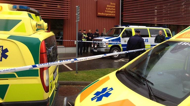 Kuvassa näkyy etualalla kaksi ambulanssia ja taustalla joukko poliiseja koulun edessä.