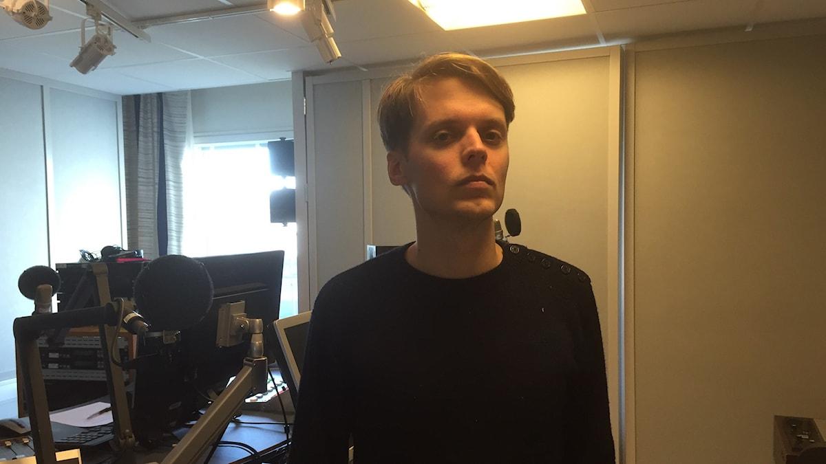 Mattias Björkas seisoo studiossa musta paita yllään. Kuva: Timo Laine/SR Sisuradio