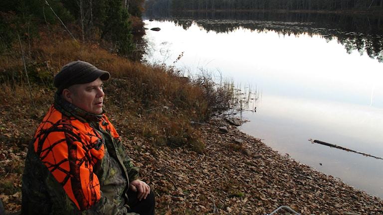 Tapani Takanen istuu järven rannassa. Hänellä on yllään oranssi ja vihreä metsästystakki ja vihreä lippis. Kuva Pekka Ranta, Sveriges Radio.