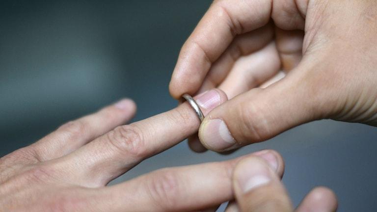 Mies pujottaa sormuksen toisen sormeen, lähikuva. Foto: KENZO / AFP / TT