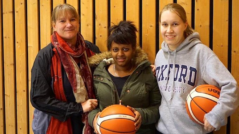 Kolme naista, kahdella kädessä koripallo
