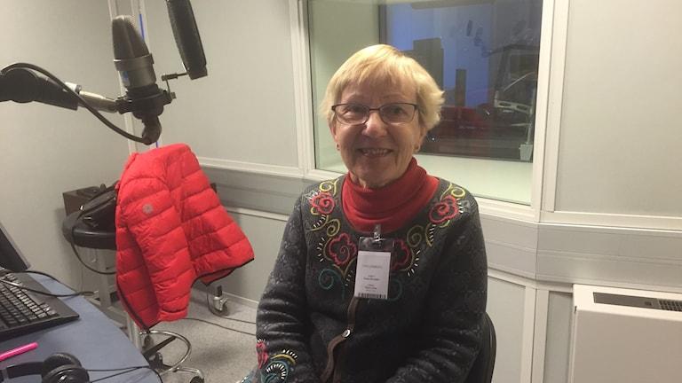 Paula Ehrnebo istuu studiossa hymyillen kukallinen neule päällään. Kuva: Timo Laine/SR Sisuradio