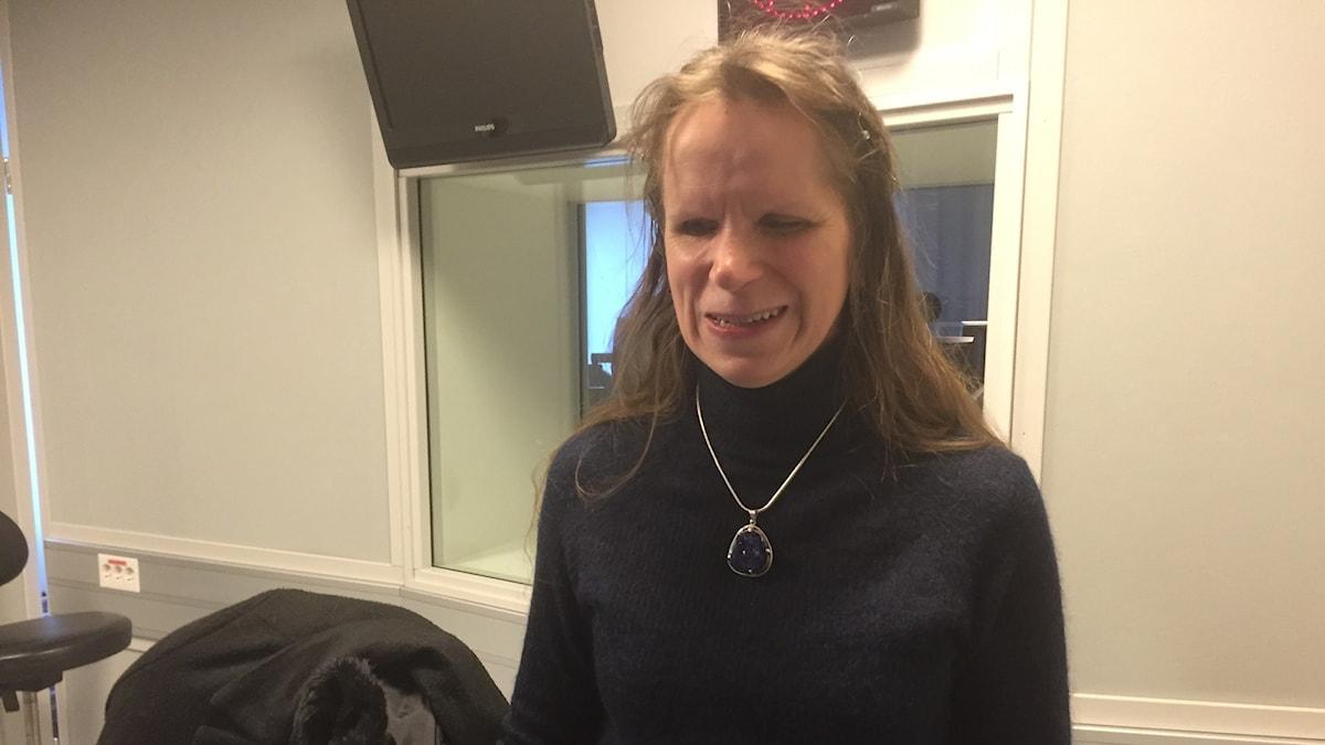 Tiina Nummi-Södergren seisoo hymyillen studiossa musta poolopaita päällään. Kuva: Timo Laine/SR Sisuradio