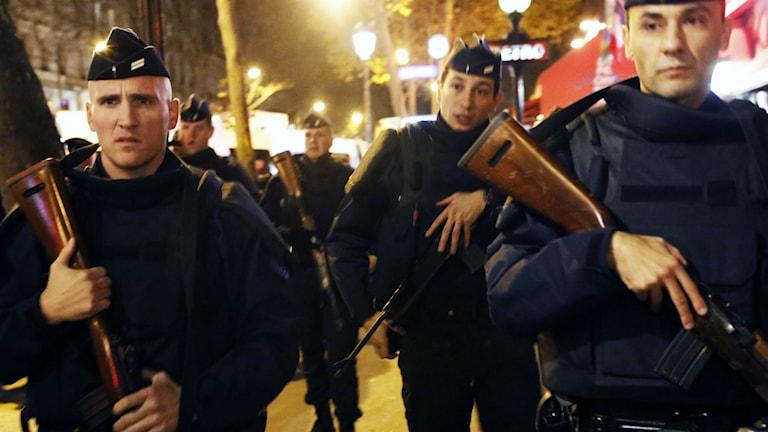 Kolme poliisia lähikuvassa. Kukin kantaa suurta asetta.