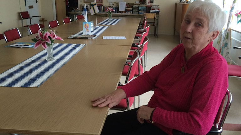 Onerva Laaksonen istuu pitkän tyhjän pöydän ääressä. Kuva:Ulla Rajakisto/Sveriges Radio Sisuradio