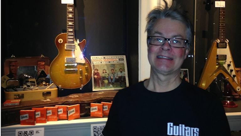 Samuel Åhden seisoo kitaravitriinin edessä, vitriinissä Gibson Les Paul -60 ja John Mayalin levy Blues Breakers. Foto: Erpo Heinolainen SR Sisuradio