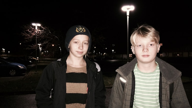 Elsa Kari ja Walter Kari seisovat pimeässä parkkipaikan vieressä. Foto: Kai Rauhansalo