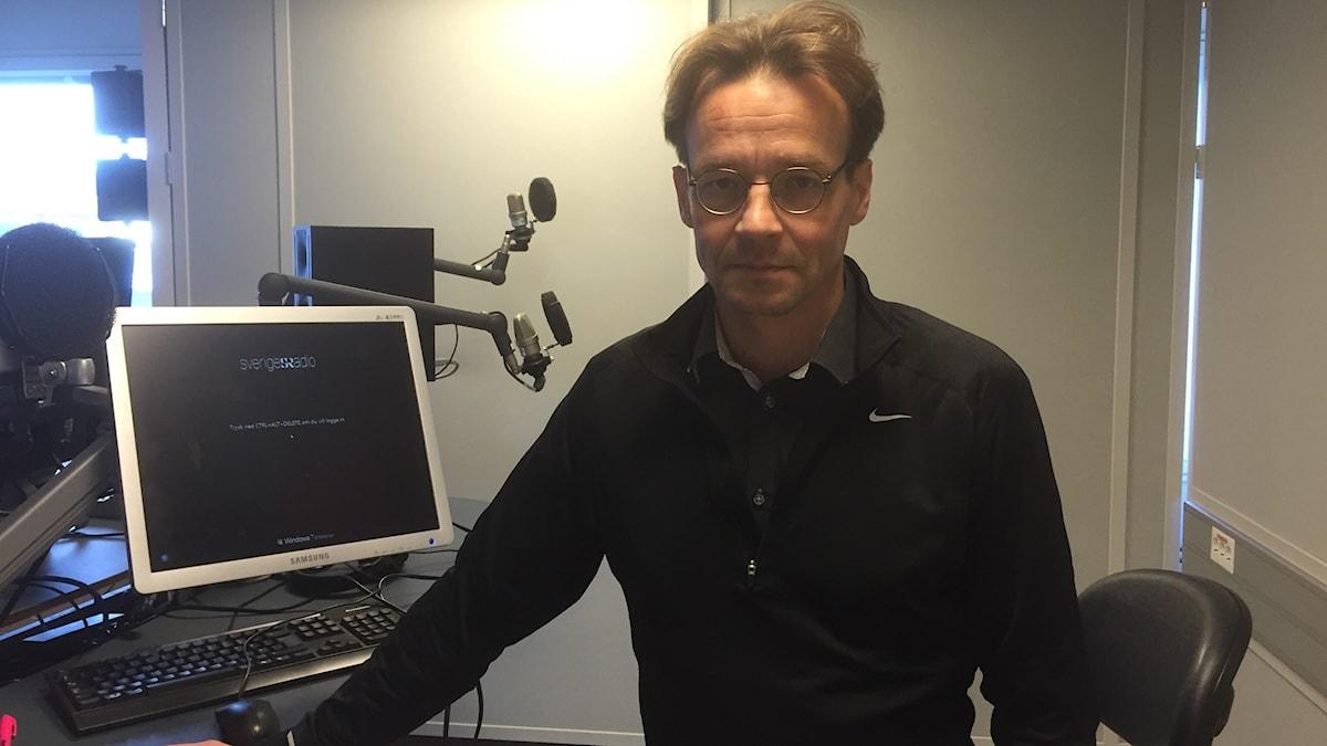 Markku Rummukainen seisoo studiossa silmälasit päässä. Kuva: Timo Laine/SR Sisuradio