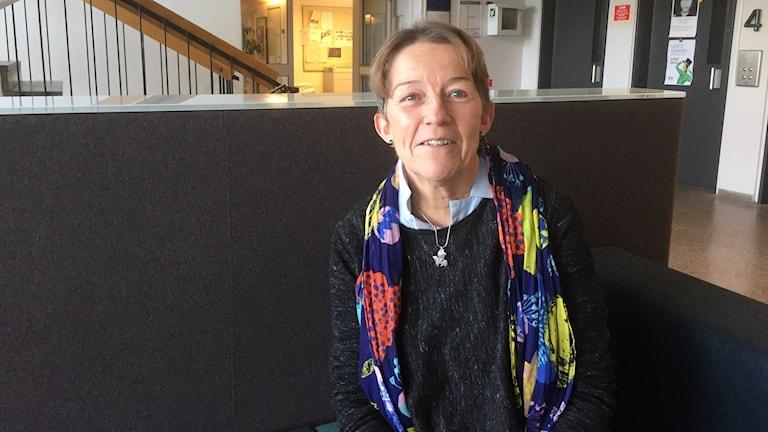 Janina Orlov istuu mustalla sohvalla värikäs huovi kaulallaan. Taustalla portaikkoa ja hissin ovet. Kuva/Blid: Timo Laine/SR Sisuradio