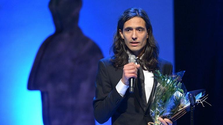 Jonas Hassen Khemiri pitää puheen saatuaan Augustpriset-palkinnon kaunokirjallisten teosten sarjassa. Tumma puku, käsissä mikrofoni ja kukkakimppu. Foto: Maja Suslin/TT