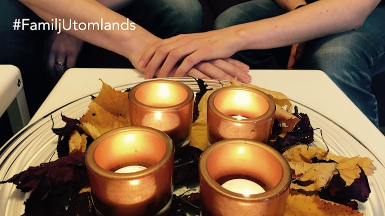 Värmeljus i förgrunden, och två händer som håller i varandra i bakgrunden. Marika Pietilä / Sveriges Radio Sisuradio